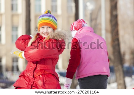 Children in winter park having fun and playing snowballs - stock photo