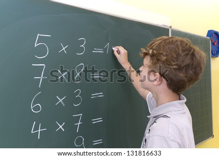Children is doing some maths at a blackboard.