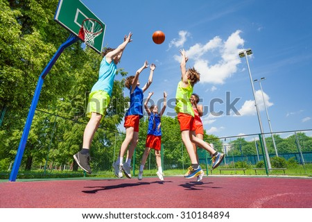 Children jump for flying ball during basketball - stock photo
