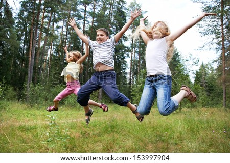 Children jump on lawn in summer forest and enjoy life in sports - stock photo