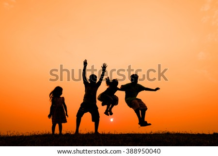 children jumping silhouette at sunset