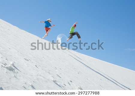 """Children jumping with bare feet down the dune. National Monument """"White Sands"""", New Mexico, United States - stock photo"""