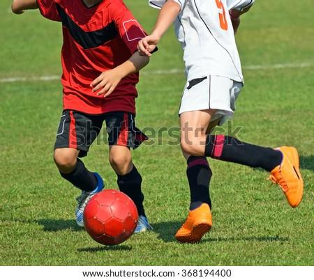 Children kick the ball at a soccer match - stock photo