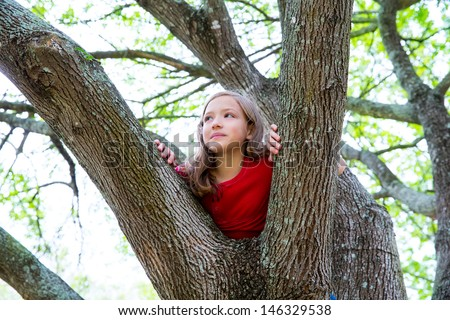children kid girl playing climbing to a tree in a park outdoor - stock photo