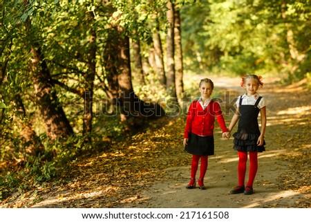 Children kid girls walking to school  in outdoor park - stock photo