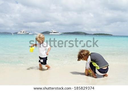 Children, kids having fun on a white sand tropical beach near Caribbean ocean - stock photo