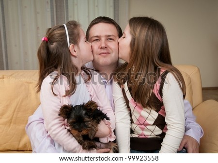Children kissing their father - indoors at home