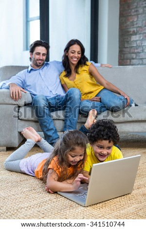 Children laying on carpet in living room using laptop while parents on the sofa - stock photo