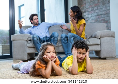 Children laying on the carpet in living room while parents arguing on the sofa - stock photo