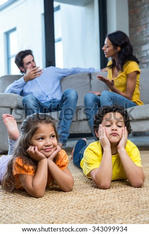 Children laying on the carpet in living room while parents talking on the sofa - stock photo
