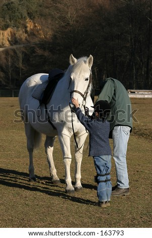 Children learning to ride a horse - stock photo
