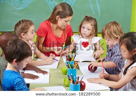 Children learning writing together in preschool with nursery teacher - stock photo