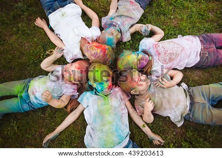 Children lie on the grass. Children painted in the colors of Holi festival lie on the grass.