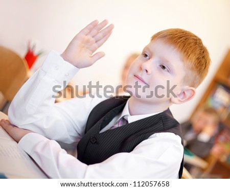 Children listening teacher and boy raising hand for answer during the lesson - stock photo