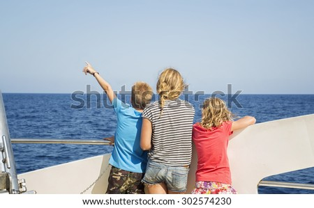 Children look at the sea from the deck of a boat