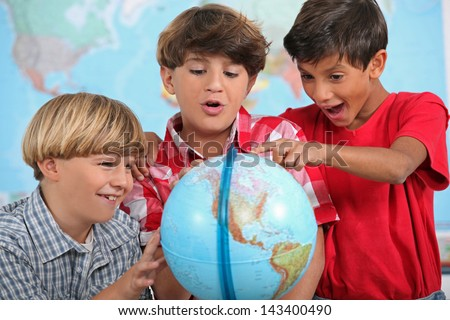 Children looking at a globe - stock photo