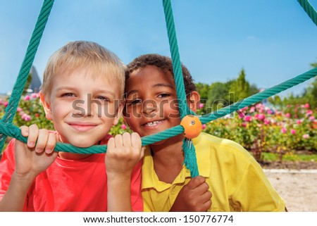 Children looking through the net at the playground - stock photo