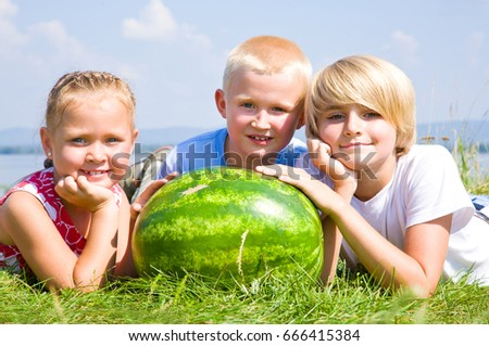 Children lying in grass with big  watermelon
