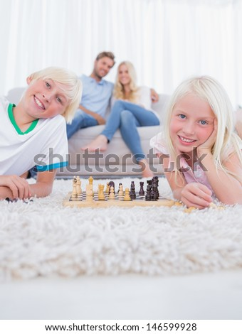 Children lying on carpet playing chess in the living room - stock photo