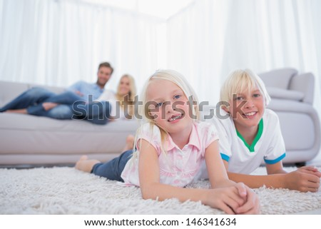 Children lying on the carpet and smiling at camera - stock photo