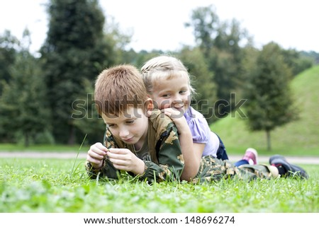 Children lying on the green grass in the park