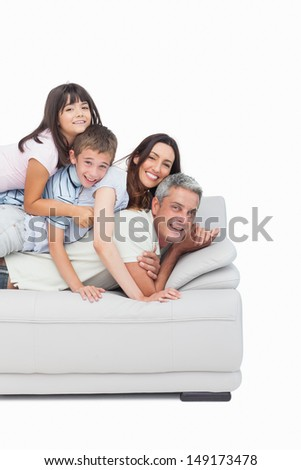 Children lying on their parents on sofa on white background