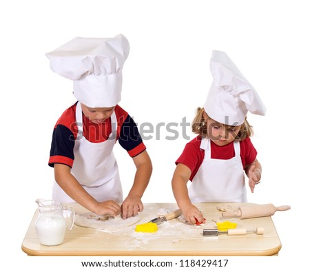 Children making christmas cookies dressed as chefs - cutting the dough to star and pine tree shapes