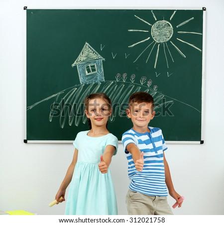 Children near blackboard at school - stock photo