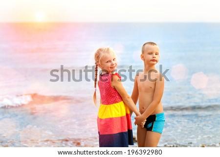children near the sea in sunset - stock photo
