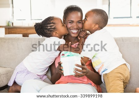 Children offering a gift to their mother in living room - stock photo