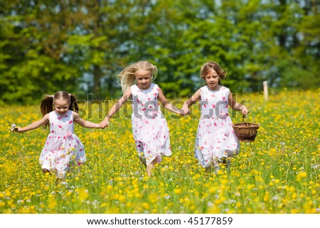 Children on a beautiful sunlit meadow in spring with a basket on an Easter egg hunt - stock photo