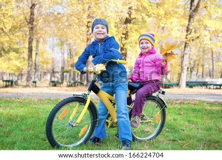 children on a bicycle in autumn park