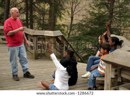 Children on a nature walk, focus on the teacher. - stock photo