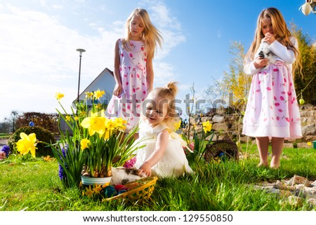 Children on an Easter Egg hunt on a meadow in spring, in the foreground a living Easter bunny is waiting - stock photo