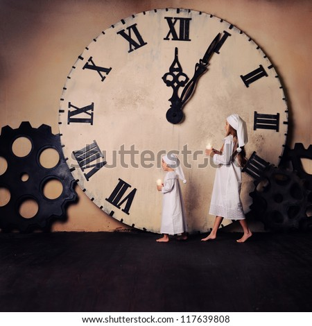 Children on Christmas go with candles. The big clock in the background. A boy and a girl in a nightgown and cap. - stock photo