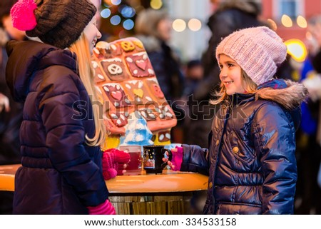Children on Christmas market with gingerbread - stock photo