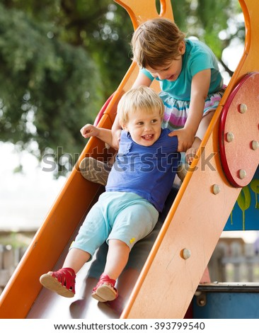 children on slide at playground area  in summer
