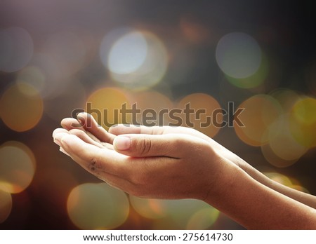 Children open empty hands with palms up. Human hands of prayer over candle light in dark room background. - stock photo