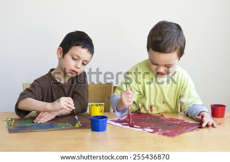 Children painting a picture with brush at home or playgroup. - stock photo