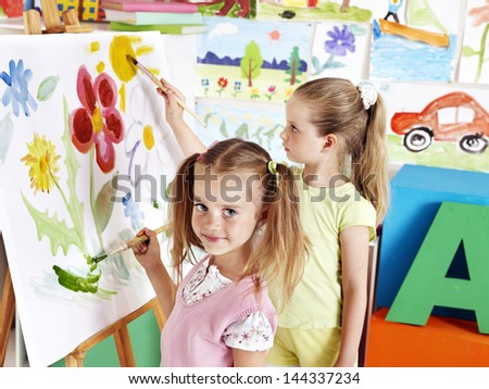 Children painting at easel in art class. - stock photo