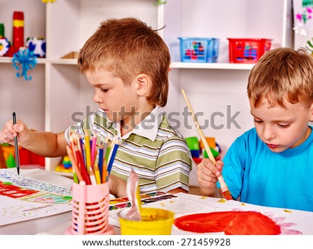 Children painting at easel in school. Education. Two boys.