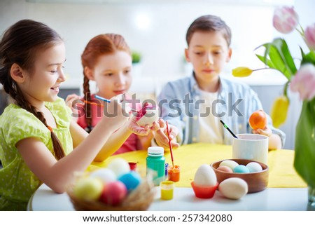 Children painting eggs at school - stock photo