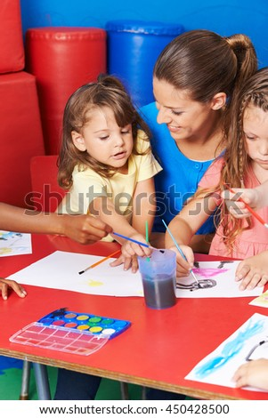 Children painting images in child care after elementary school with teacher - stock photo