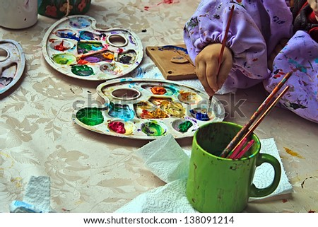 Children painting pottery at a workshop organized by the International Children's Day in Timisoara, Romania. - stock photo