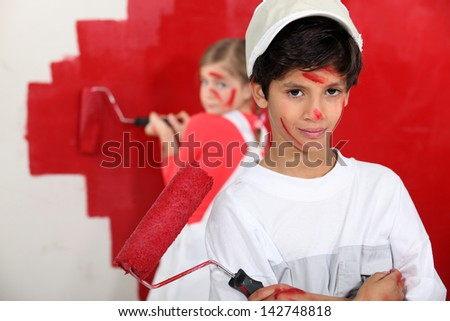 Children painting wall in red - stock photo