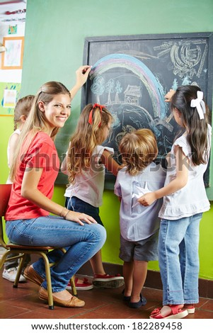 Children painting with chalk on blackboard together with a nursery teacher - stock photo