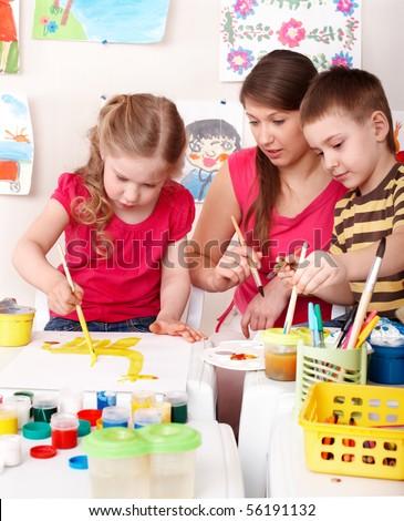 Children painting with teacher. Child development. - stock photo
