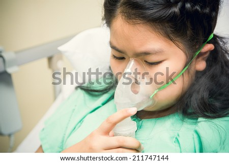 children patients on bed with oxygen mask in hospital  - stock photo