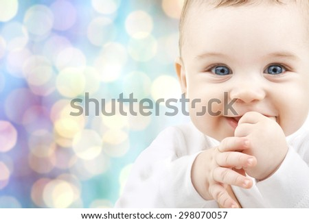 children, people, infancy and age concept - beautiful happy baby boy over blue holidays lights background