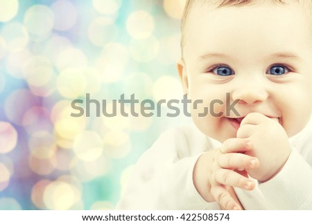 children, people, infancy and age concept - beautiful happy baby boy over blue holidays lights background - stock photo
